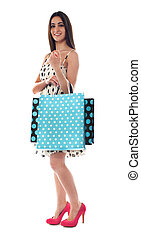 Glamorous female carrying shopping bags
