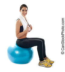 Female fitness trainer sitting on ball isolated against...