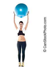 Gorgeous fit lady holding pilate ball over her head isolated...