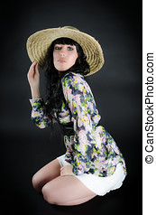 Woman in straw hat posing on black background
