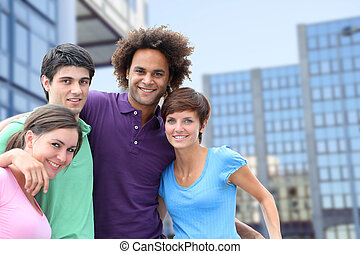 Group of friends standing in front of modern buildings in...
