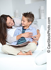 Little blond boy sitting on sofa with his mother