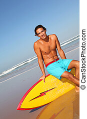Handsome man sitting on his surfboard
