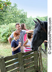 Parents and children petting horses in countryside