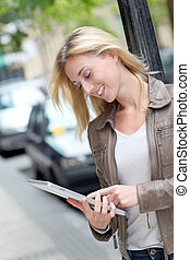 Beautiful woman using electronic tablet in town