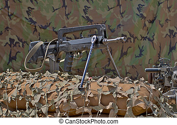firearm FAMAS on a background of camouflage tent
