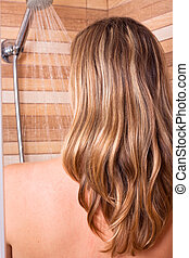 Woman with highlighted hair in shower - Young woman with...