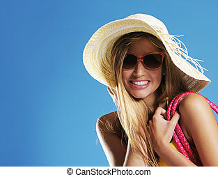 Summer girl - Smiling young woman against blue background,...