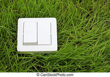 light switch on a green grass background - ecological...