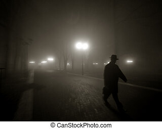 misty night - A silhouette of a man wearing a hat in the...
