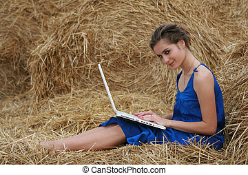 Country girl with laptop sitting at haystack looking to...