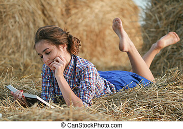 Country girl reading book lying at haystack - Country style...