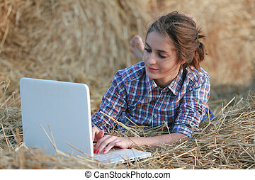 Country girl with laptop at haystack - 26-years old brunette...