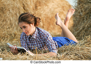 Country girl lying with book at haystack - 26 years old...