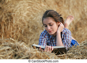 Country girl reading book lying at haystack - 26 years old...