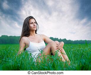 girl enjoying summer - beautiful girl relaxing in a field
