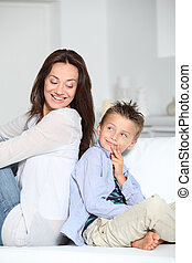 Little blond boy sitting on sofa with mom