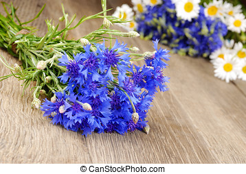 Fresh cornflower and chamomile flowers on the wooden...