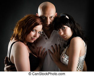 Two girls and one man in dark portrait - Man with shaved...