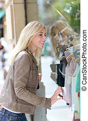 Woman standing in front of shopping windows