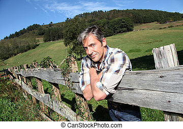 Portrait of handsome breeder leaning on fence