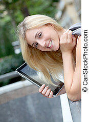 Beautiful woman with electronic tablet in town