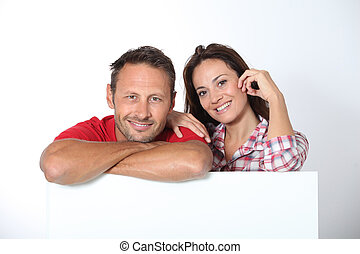 Couple showing white board for message