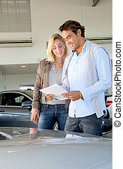 Couple reading car documentation in showroom