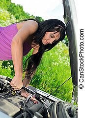 Woman repairing broken car with a socket spanner wrench.