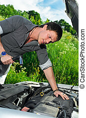 Young man repairing  broken car with a socket spanner wrench.