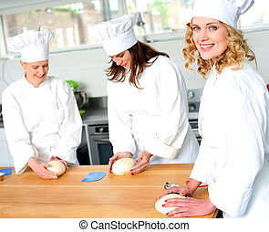 Female chefs at work in a restaurant kitchen Kneading dough