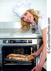 Freshly made baguette is ready for you - Female chef taking...