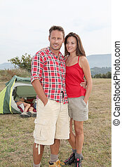 Couple standing in front of camping tent