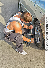 Mechanic fixing a tire on a road