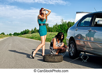 Two girls are fixing a changing a tire