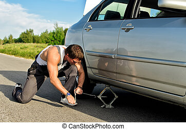 Mechanic lifting a car with jack-screw