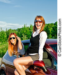 Two pretty happy girls in the car Concept of carefree...