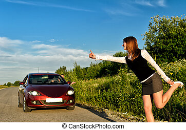Young pretty girl hitchhiking a red car