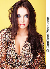 Beautiful busty brunette woman in an animal print blouse...