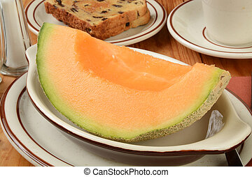 Cantaloupe - A wedge of fresh cantaloupe with raisin bread...