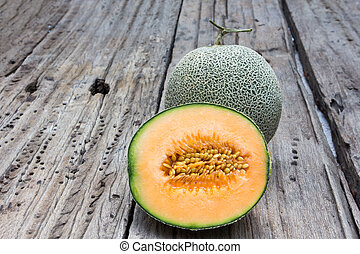 cantaloupe melon slices on old wood background
