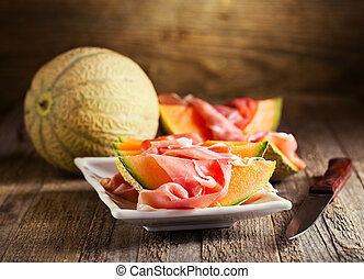 cantaloupe melon with prosciutto on wooden background