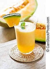 Cantaloupe smoothie in a glass by fresh cantaloupe
