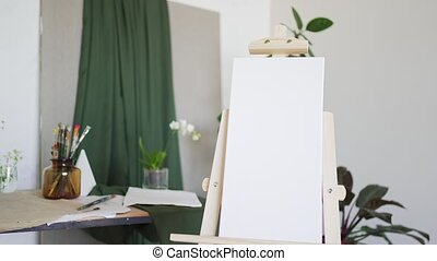 Canvas on easel. Blank white banner. No people.