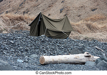 Canvas tent on the rocky shore