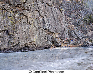 canyon of mountain river in winter scenery with distant rock climbers - Poudre River at Picnic Rock above Fort Collins, Colorado