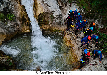 canyoning with a group of people at a waterfall