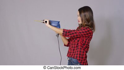Capable attractive young woman holding a drill