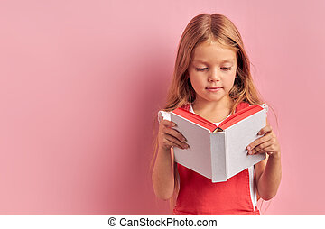 Capable little girl in red overalls reading book isolated over pink background