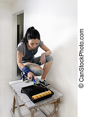Capable young woman painting a wall